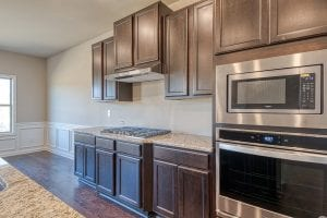 New Home Plan by Chafin Communities The Denton with Brown Cabinets in Upgrade Gourmet Kitchen