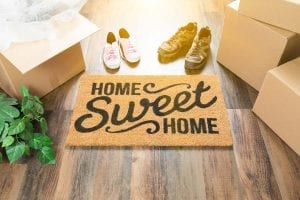 Home Sweet Home Welcome Mat, Moving Boxes, Women and Male Shoes and Plant on Hard Wood Floors.